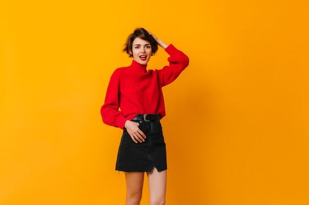 Femme insouciante en jupe debout sur un mur jaune
