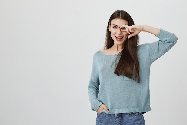 Femme insouciante montrant un signe correct sur les yeux et souriant