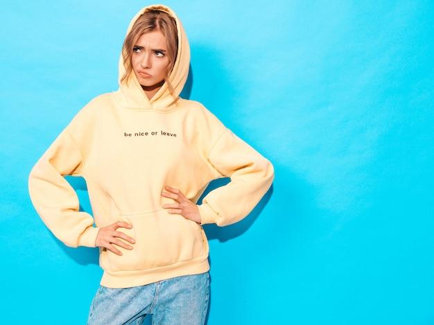 Femme insouciante posant près du mur bleu en studio. modèle positif s'amusant, elle n'est pas contente de quelque chose