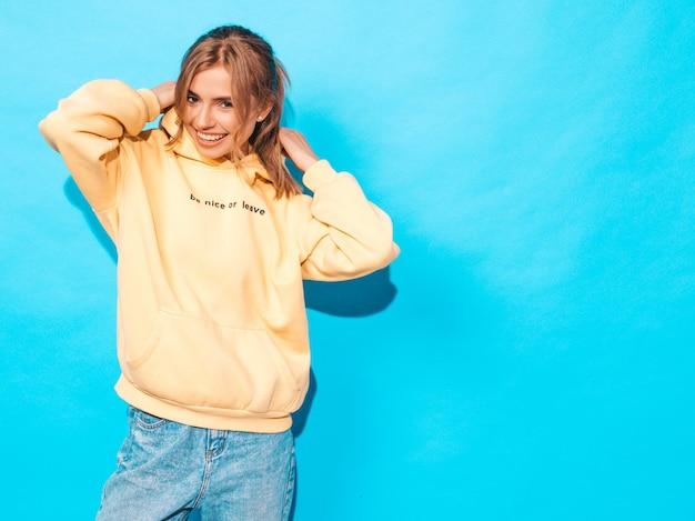 Femme insouciante posant près du mur bleu en studio. modèle positif s'amusant