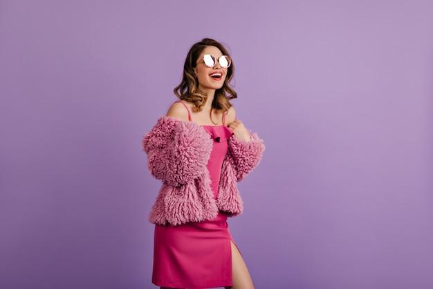 Femme insouciante qui pose en veste et lunettes de soleil