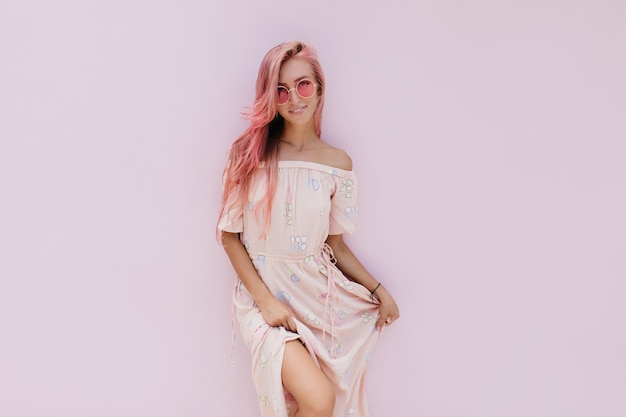 Femme insouciante en robe d'été élégante posant avec un sourire d'intérêt.