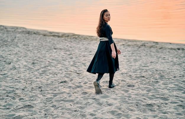 Femme insouciante en robe noire et longs cheveux bouclés marchant au coucher du soleil sur la plage. concept de vie saine de vitalité de vacances