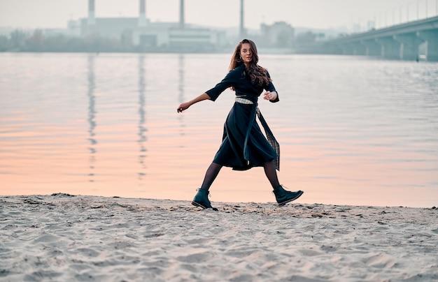 Femme insouciante en robe noire marchant au coucher du soleil sur la plage. concept de vie saine de vitalité de vacances