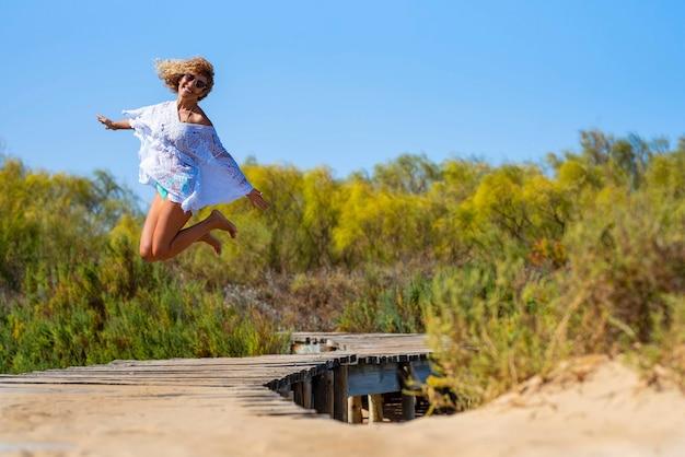 Femme insouciante sautant pieds nus dans l'air sur une passerelle surélevée menant vers la forêt naturelle. femme folle sautant sur un pont surélevé menant aux bois.