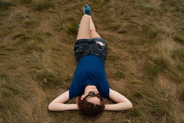 Femme insouciante se détendre sur l'herbe pendant la journée d'été ensoleillée portant des lunettes et des shorts.