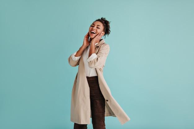 Femme insouciante en trench-coat en riant à l'avant