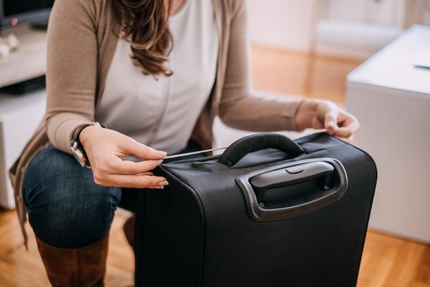 Femme inspectant la mesure de bagages à main à l'aide de ruban à mesurer.