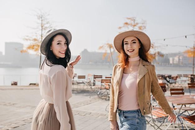 Femme inspirée en chemisier blanc regardant par-dessus l'épaule avec sourire, marchant avec un ami au gingembre