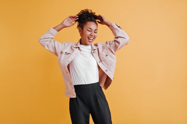 Femme inspirée en veste posant avec les mains vers le haut