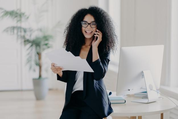 Une femme intelligente détient des documents papier et vérifie des informations