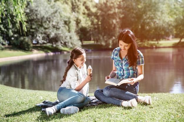 Une femme intelligente est assise au bord d'un petit lac avec sa fille et lit un livre. son enfant est assis à côté d'elle et mange de la glace. la fille regarde ce que maman fait en ce moment.