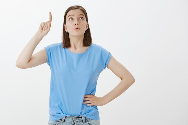 Une femme intelligente excitée a une bonne idée, en levant le doigt, en suggérant un plan