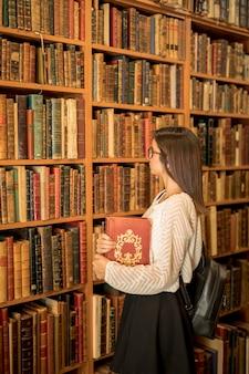Femme intelligente avec livre dans la bibliothèque