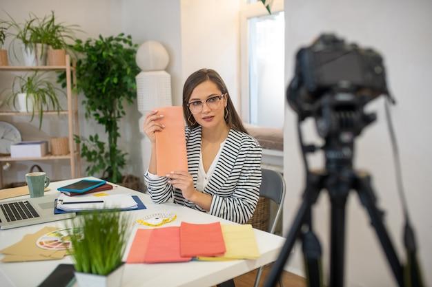 Femme intelligente sérieuse parlant de différents échantillons tout en ayant un tutoriel pour les jeunes designers