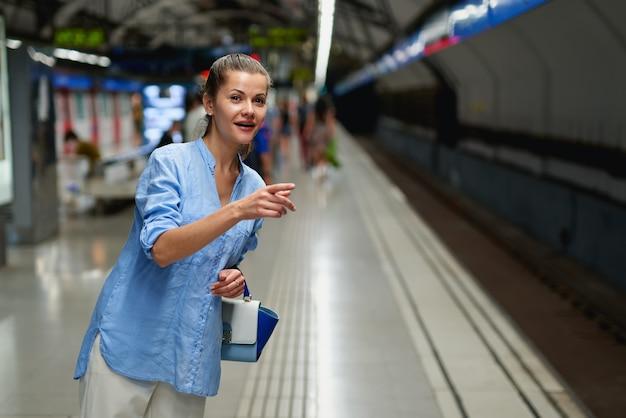 Femme à l'intérieur du métro en attente sur le quai d'une gare ferroviaire pour l'arrivée du train.