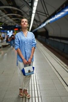Femme à l'intérieur du métro en attente sur le quai d'une gare pour le train d'arriver.