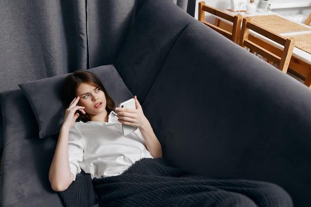 Femme à l'intérieur se trouve sur le canapé avec un téléphone portable à la main