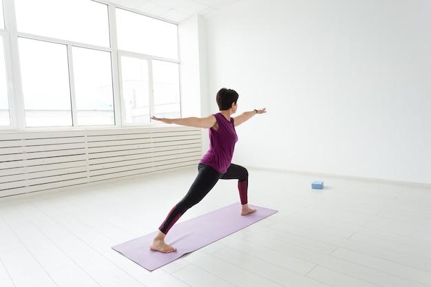 Femme intermédiaire faisant du yoga et essayant de faire une asana