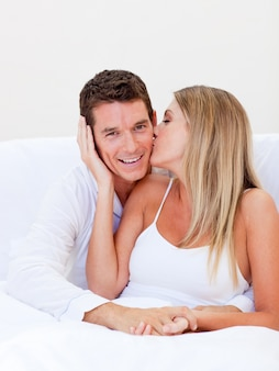 Femme intime embrasser son mari assis sur le lit