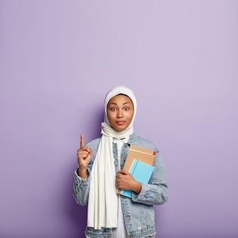 Une femme intrigante surprise en couvre-chef pointe vers le haut et regarde avec intérêt, montre un espace vide au-dessus pour votre publicité ou information, porte un journal et un cahier à spirale. religion musulmane