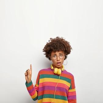 Une femme intriguée et perplexe observe une chose intéressante, pointe au-dessus avec son index, montre de l'espace pour votre promo, porte des lunettes rondes et un pull coloré