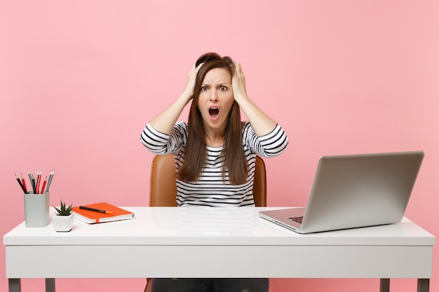 Femme irritée criant accrochée à la tête s'asseoir et travailler au bureau blanc avec un ordinateur portable contemporain isolé sur fond rose pastel. concept de carrière d'entreprise de réalisation. copiez l'espace pour la publicité.