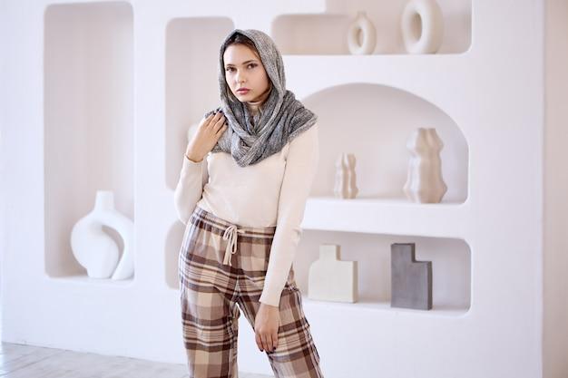 La femme de l'islam dans le foulard se tient dans le salon