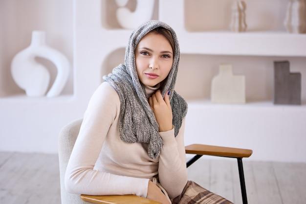 Femme islam souriante en hijab est assise dans le salon