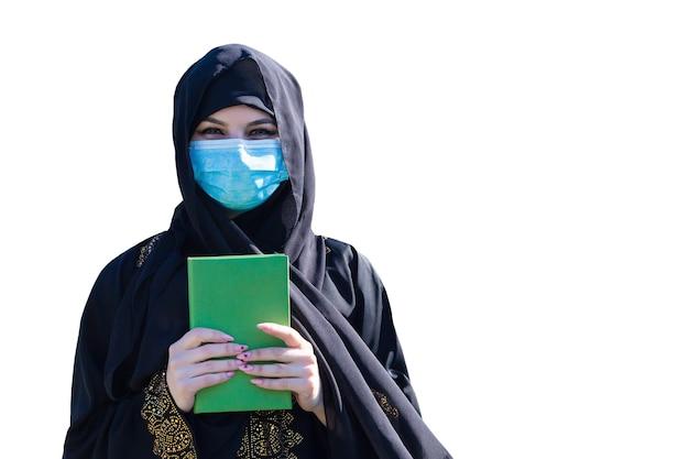 Femme islamique avec le coran dans ses mains. masque de protection médicale