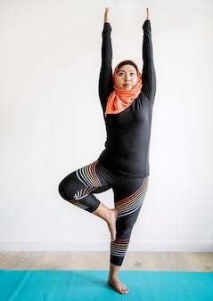 Femme islamique, faire du yoga dans la chambre