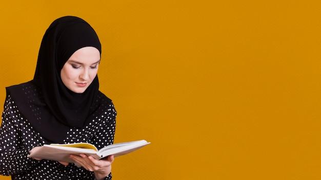 Femme islamique avec livre de lecture de foulard devant le fond avec espace de copie