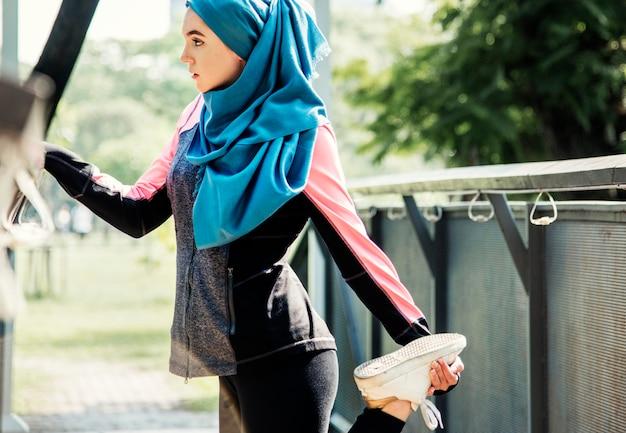 Femme islamique qui s'étend après l'entraînement au parc