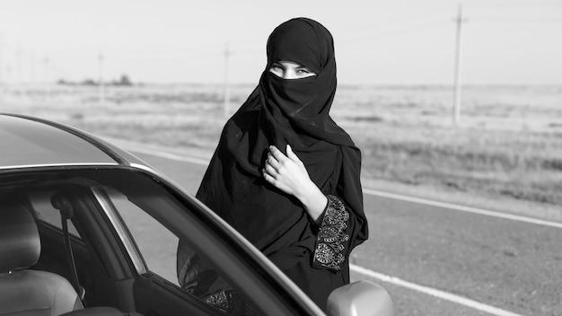 Femme islamique sur une route vide près de la voiture. noir et blanc
