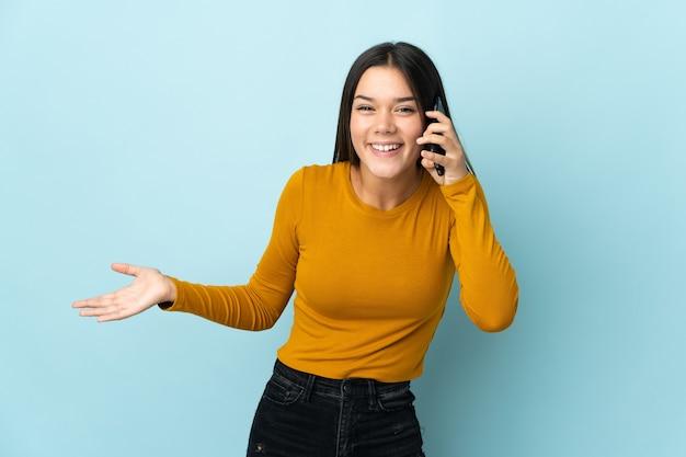 Femme isolée sur bleu en gardant une conversation avec le téléphone mobile avec quelqu'un