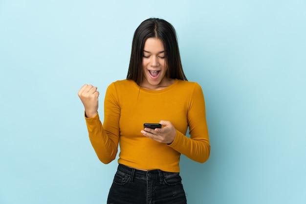Femme isolée sur bleu surpris et envoyant un message