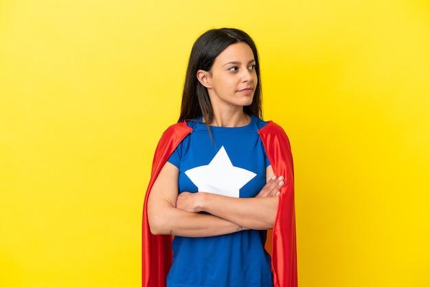 Femme isolée sur fond jaune en costume de super-héros avec les bras croisés