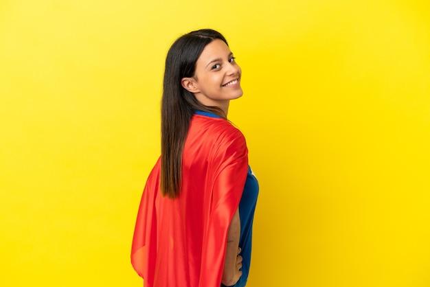 Femme isolée sur fond jaune en costume de super-héros et faisant la pose avec les bras à la hanche et souriant