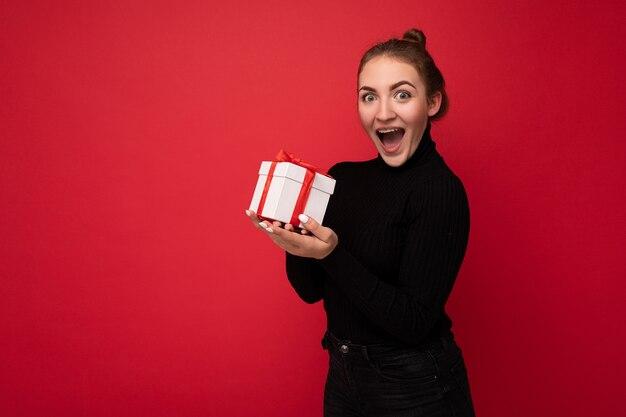 Femme isolée sur mur coloré portant une tenue à la mode look holding gift box