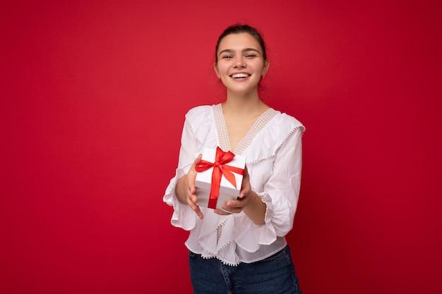 Femme isolée sur un mur coloré portant des vêtements décontractés élégants tenant une boîte-cadeau et. espace libre