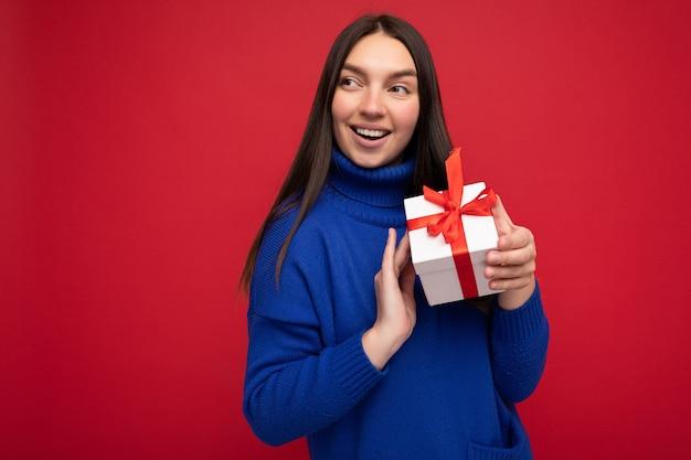 Femme isolée sur un mur coloré portant des vêtements décontractés élégants tenant une boîte-cadeau et regardant sur le côté.