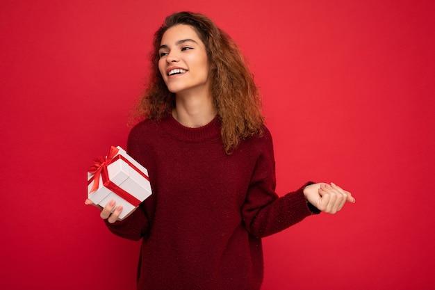 Femme isolée sur un mur de fond coloré portant des vêtements décontractés élégants tenant une boîte-cadeau et regardant sur le côté.