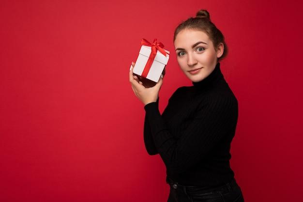 Femme isolée sur mur rouge portant un pull noir tenant une boîte-cadeau blanche avec ruban rouge