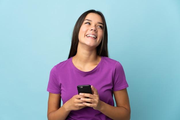 Femme isolée sur rose à l'aide de téléphone mobile et levant