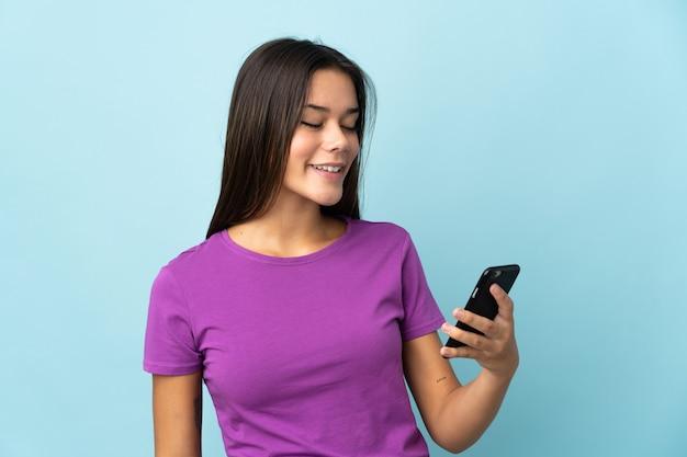 Femme isolée sur rose envoyant un message ou un e-mail avec le mobile
