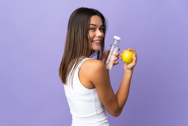 Femme isolée sur violet avec une pomme et une bouteille d'eau