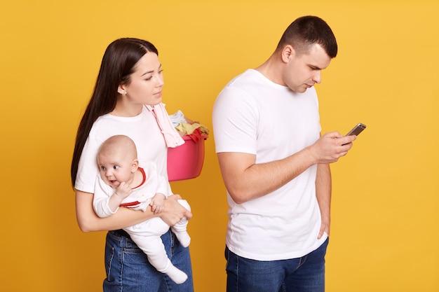 Femme jalouse espionnant le téléphone de son partenaire posant derrière lui avec un nouveau-né et un bassin avec du linge alors que l'homme vérifie son réseau social