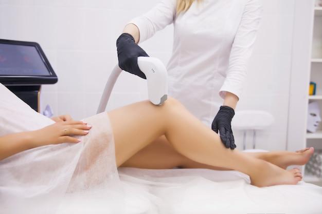 Femme, jambes, femme, professionnel, clinique beauté, pendant, épilation laser