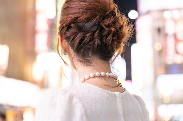 Femme japonaise avec collier glamour dans les rues de tokyo, japon. vue arrière