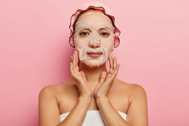 Une femme japonaise sérieuse met un masque nourrissant sur le visage, applique une feuille de produit hydratant sur la peau, porte un bonnet de bain, pose contre un mur rose. concept de traitement de la féminité, de la cosmétologie et du spa